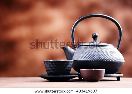 Black pialats and teapot on blurred background