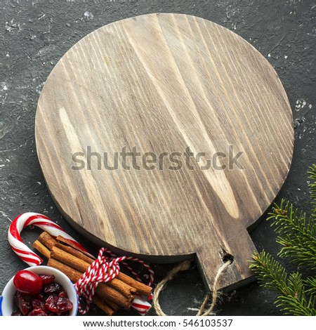 Black slate for notes with fir branch and candy stick on a simple wooden background. Top view.