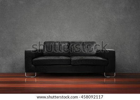 Black sofa with wooden floor concrete wall in empty living room interior loft style