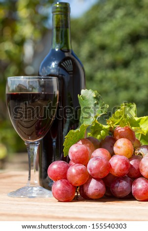 Black wine glass with freshly harvested grapes