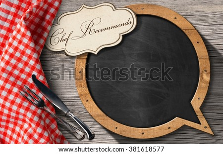 Blackboard in the shape of speech bubble and label with text Chef Recommends and silver cutlery on a wooden table with a checkered tablecloth