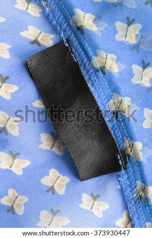 Blank black clothes label on blue chiffon as a background