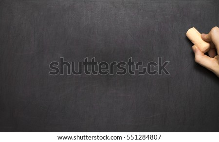 Blank blackboard / chalkboard, hand writing on black chalk board holding chalk, great texture for text.
