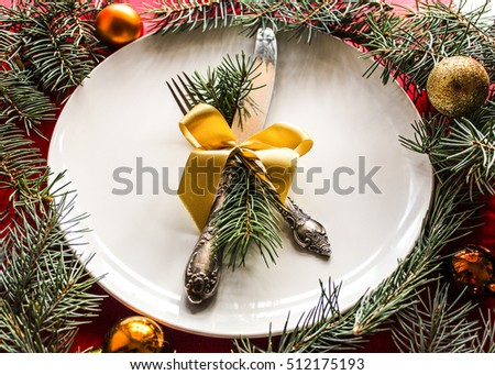blank Christmas plate with knife and fork and golden balls. Christmas table setting place with festive decorations. Christmas dinner background top view. blank Christmas plate with knife and fork