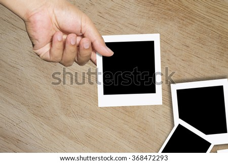 Blank instant photo in man's hand - place your own picture on it.