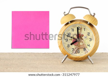 Blank note paper and vintage wooden alarm clock on table, background, template