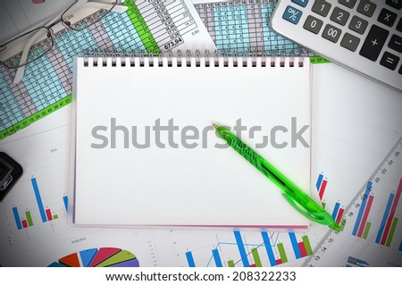 blank notebook and financial charts