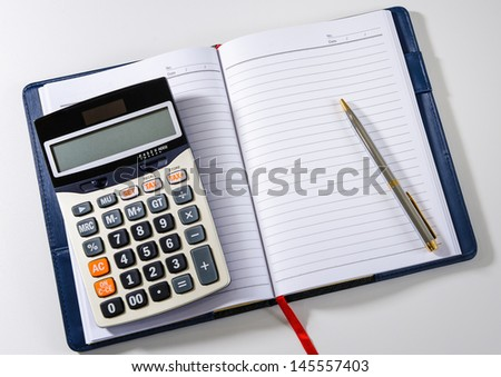 Blank notebook with pen and calculator on the desk