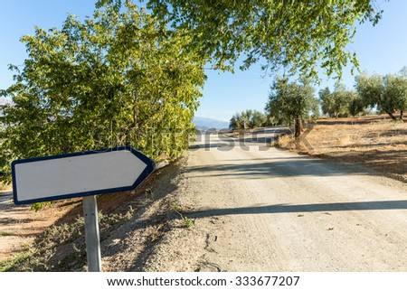 Blank road sign by side of dry dusty road with olive trees and mountains in the distance