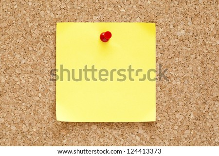 Blank yellow sticky note pinned on a cork bulletin board.
