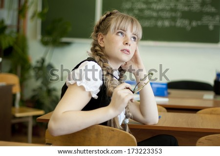 blond girl in school at the desk on board background