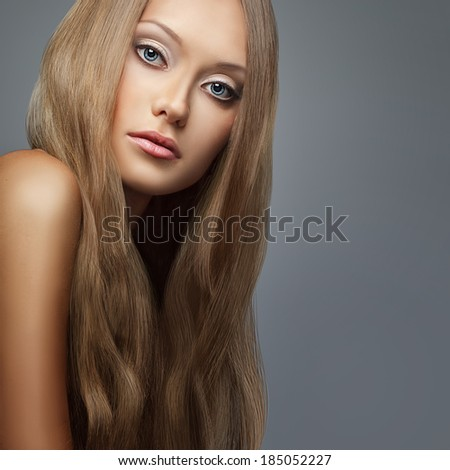 blond hair. Beautiful woman with long hair over gray