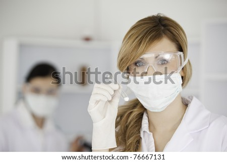 Blond-haired scientist holding a test tube looking at the camera in a lab