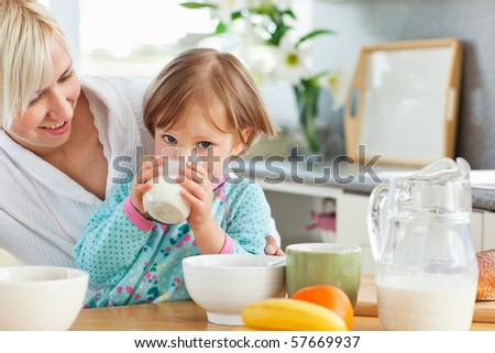 Blond mother and daughter having breakfast in the kitchen