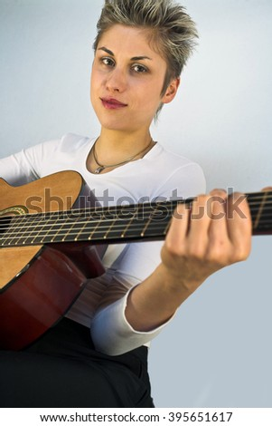 Blond short hair woman woman with white Tshirt playing acoustic guitar