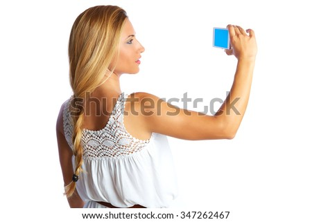 Blond tourist girl taking photos with smartphone on white background and braid