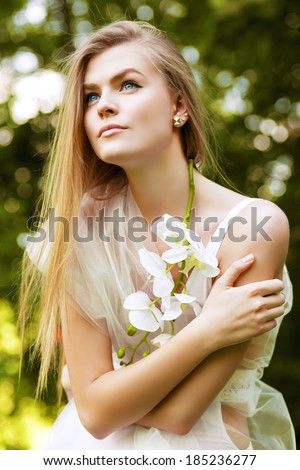 blond woman in white among green trees