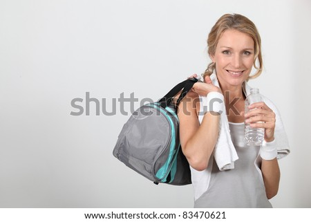 Blond woman wearing sportswear holding water bottle with bag over shoulder
