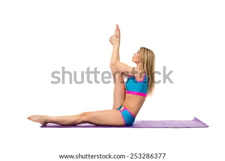 Blonde doing stretching exercise on training mat