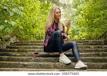 Blonde female using a smartphone and sits on Longboard on the steps.