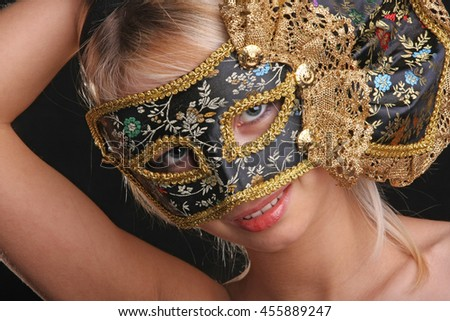 blonde flirts in the Venetian mask on black background