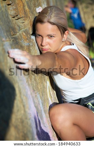 Blonde girl climbing on the rock. Close.