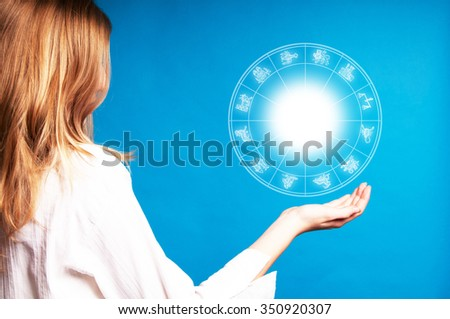 blonde girl holding an astrology chart in the air