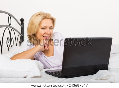 Blonde mature woman with laptop laying on white sheet in her bed at home