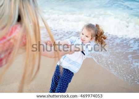Blonde mother and little cute girl play at the beach. Travel and Vacations.