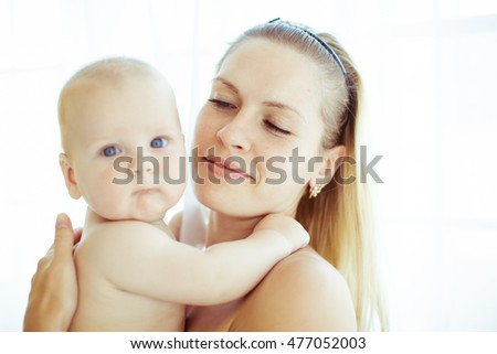 Blonde mother holds her little child