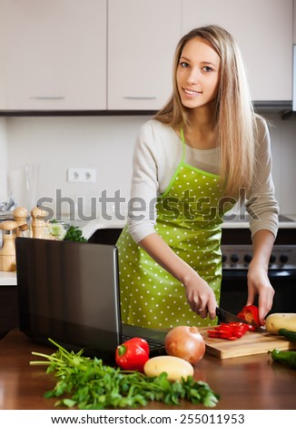 Blonde woman cooking  with laptop in home kitchen