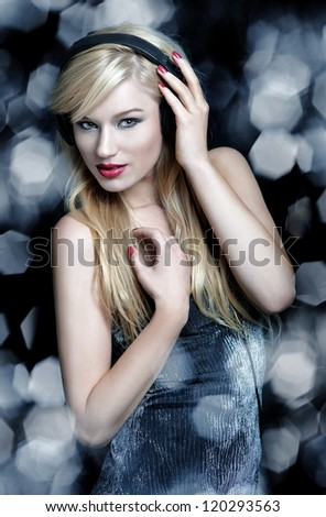 Blonde woman dancing with headphones on silver background
