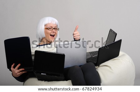 blonde woman surfing internet with laptops, isolated on grey