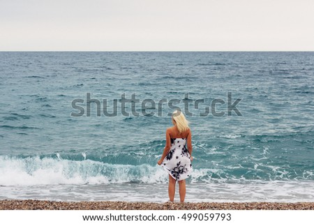 blonde women with blowing dress on beach