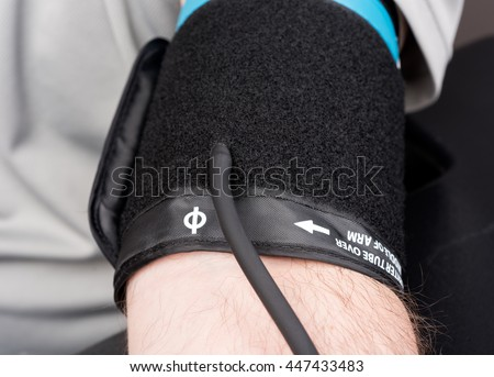 Blood pressure cuff on a man's arm for blood pressure test.
