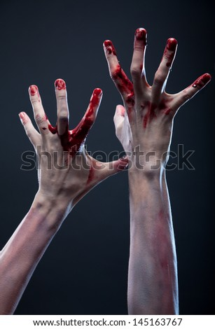 Bloody zombie hands, studio shot over gray background
