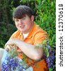 Blooming wisteria adds splash of purple to garden photo.  Male teen is dressed in bright orange polo. - stock photo