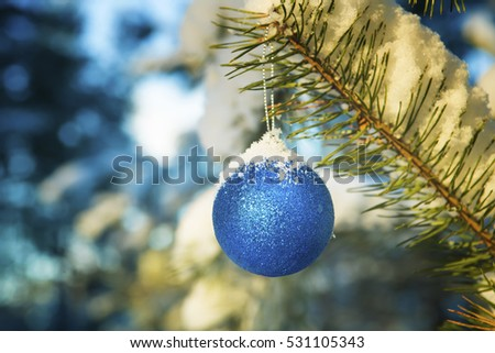 Blue ball on a  branch in the snow-covered wood. Christmas background