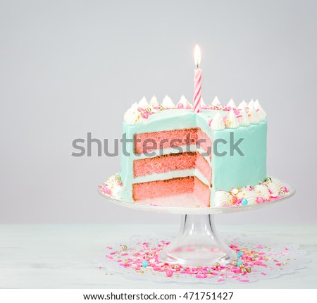 Blue buttercream birthday cake with pink layers and sprinkles.