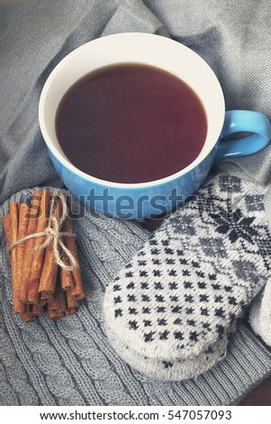 Blue Cup of tea with plaid on  wooden Board Christmas background with space.gloves ,cinnamon
