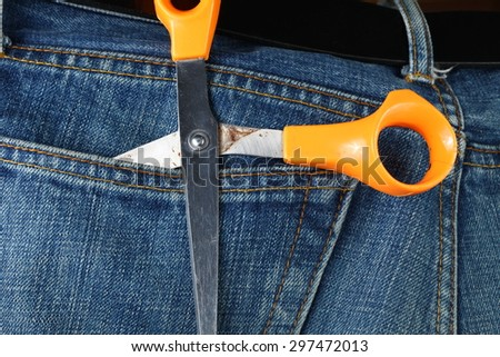 Blue denim jeans in dark color in the scene present the old denim look at the back pocket part with scissors inside.