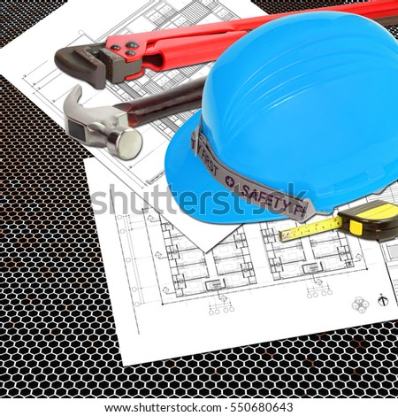 Blue Helmet of foreman or guest constructor with blueprints building construction and tools, metal tape measure, hammer, wrench