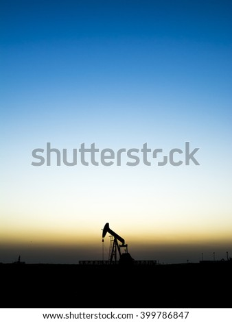 Blue hours after sunset and silhouette of crude oil pump in the oil field