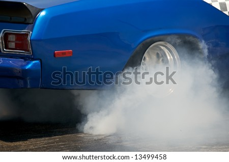 Blue race car burns rubber off its tires in preparation for the race