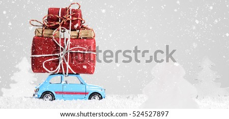Blue retro toy car delivering Christmas or New Year gifts on gray background