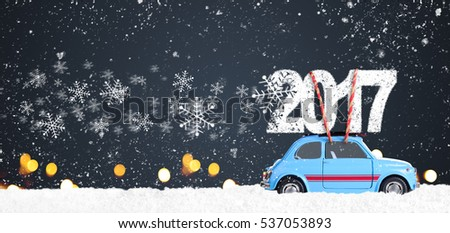 Blue retro toy car delivering Christmas or New Year 2017 on festive gray background