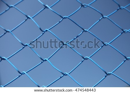 Blue steel wire mesh fence. Metal fence grid against a blue sky