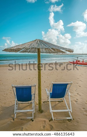 Blue sunbeds and umbrella on a sunny beach.