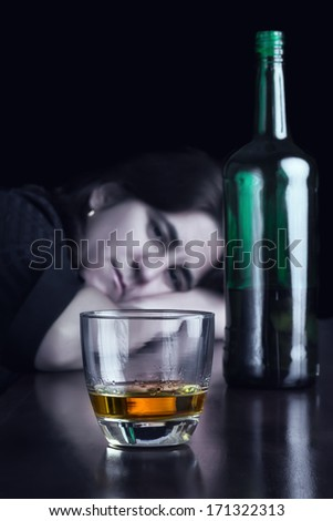 Blue toned dark image of a sad drunk woman staring at a glass of whisky