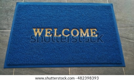 blue welcome mat, carpet welcome in front of toilet.